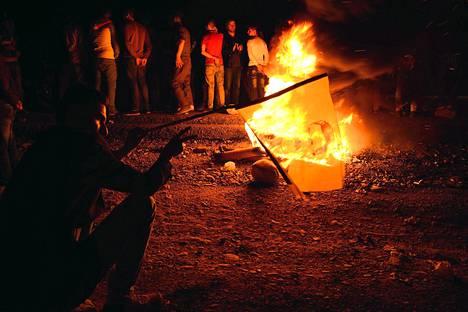 Turkin kurdit juhlivat peshmerga-taistelijoiden saapumista Irakin vastaisen rajan yli Haburissa 28. lokakuuta. Kuvassa mies heiluttaa Turkin vangitseman kurdijohtajan Abdullah Öcalanin lippua. Raskaasti aseistautuneet kurditaistelijat ovat matkalla terroristijärjestö Isisin piirittämään Kobanin rajakaupunkiin Syyriaan. Kobania puolustavat kurdit ovat odottaneet peshmergoja viime viikosta lähtien, jolloin Turkki antoi kurditaistelijoille luvan käyttää aluettaan kaupunkiin pääsemiseksi.