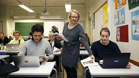 Oskar Maurula (vas.) ja Mikael Lindberg saavat Hanna Kallungilta (kesk.) äidinkielen koemateriaalin Etu-Töölön lukiossa.