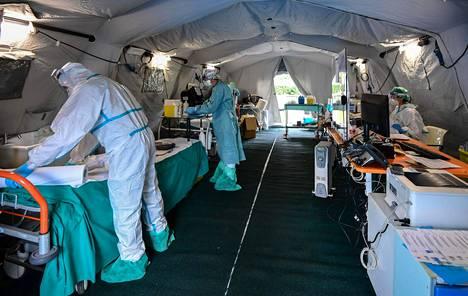 Brescian sairaalan edustalle pystytetyssä väliaikaisessa hätäsairaalassa hoidetaan uusia koronatapauksia. Sairaalan työntekijät ovat pukeutuneet suoja-asuihin.