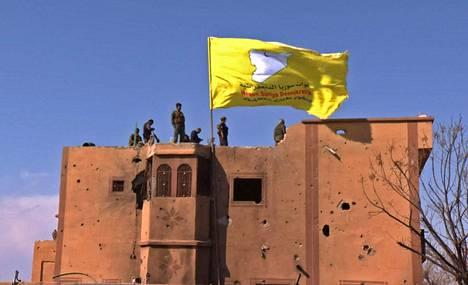 Kurdien SDF-joukkojen keltainen lippu rakennuksen katolla Baghuzissa lauantaina.