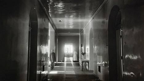Lapinlahden sairaalan käytävä 1900-luvun alussa. Käytävällä seisoo miespotilas ja taaempana  sairaanhoitaja.