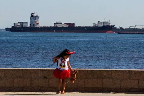 Pieni tyttö leikki merenrannan parkkipaikalla Long Beachissa Kaliforniassa viime viikon perjantaina. Taustalla öljyvarastona toimiva tankkeri. Merivartioston mukaan kaikkiaan 27 öljytankkeria oli ankkuroitunut varastointitarkoituksessa Etelä-Kalifornian rannikolle.