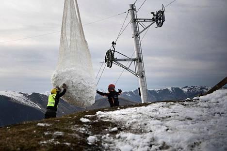 Työntekijät käsittelivät helikopterista roikkuvaa verkkoa, jolla siirrettiin lunta Luchon-Superbagnèresin laskettelukeskuksessa Ranskassa lauantaina.