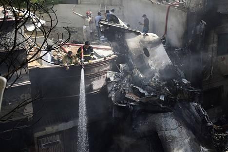 Pelastustyöntekijät ruiskuttivat vettä koneen hylyn päälle.