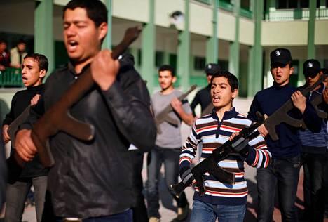 Gazalaislukiolaisia harjoitteli asejäljitelmillä sotilastyyliin koulun pihalla Khan Younisissa maaliskuussa.