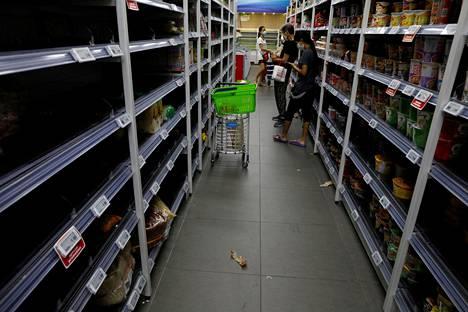 Kauppojen hyllyt olivat tyhjentyneet ihmisten hamstrattua peruselintarvikkeita Singaporessa perjantaina.