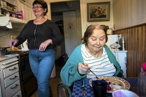 Kodinhoitaja Terttu Granroth auttaa 79-vuotiasta Senja Bundaa Helsingin Pajamäessä.