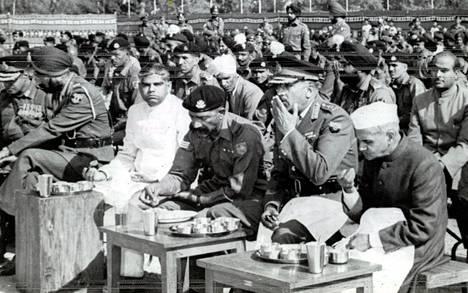 Intian pääministeri Lal Bahadur Shastri (oikealla) jakaa vaatimattoman kenttäaterian 4000 intialaisen sotilaan kanssa New Delhissä Armeijan päivän juhlallisuuksissa, Shastrin vieressä istuu Intian puolustusvoimien ylipäällikkö kenraali J. M. Chauduri.