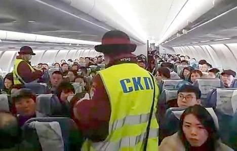 Venäläiset terveysviranomaiset mittasivat Kiinasta tulleiden lentomatkustajien ruumiinlämpöjä koneen sisällä Vnukovon lentokentällä viime torstaina. Kuva uutistoimisto Tassin välittämältä videolta.