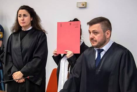 Syytetty Jennifer W. kätki kasvonsa oikeudenkäynnissä 9. huhtikuuta Saksan Münchenissä. Puolustusasianajajat Sera Basay-Yildiz (vas.) ja Ali Aydin saapuivat oikeussaliin hänen kanssaan.