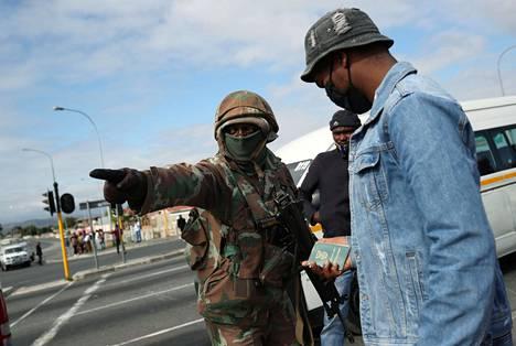 Sotilas ohjeisti matkustajaa tarkastuspisteellä Kapkaupungissa viime keskiviikkona.