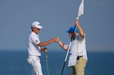 Major-kilpailuissakin tuomarina toiminut Arto Teittinen (oik.) häärii Omanin kilpailussa Oliver Lindellin caddiena.