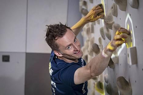 Professori Perttu Hämäläinen kiipeilyseinällä, joka hyödyntää konenäköön perustuvaa teknologiaa.