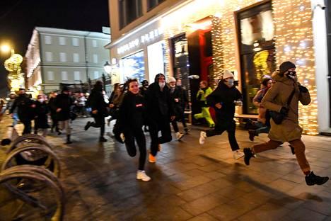 Ihmiset juoksivat mielenilmauksen aikana Moskovan keskustassa varhain aamuöllä keskiviikkona.