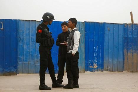 Poliisi puhutti uiguri-miehiä Xinjiangin autonomisella alueella sijaitsevassa Kašgarissa maaliskuussa 2017.