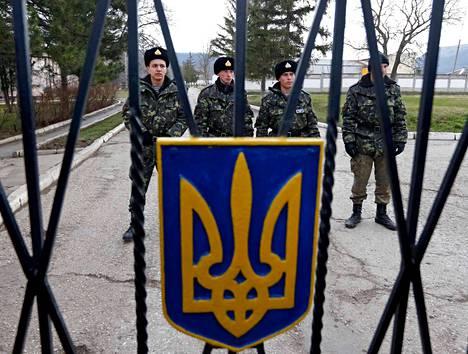 Ukrainalaiset sotilaat vartioivat tukikohtaansa Simferopolin kaupungin lähellä sunnuntaina. Etualalla Ukrainan kolmikärkivaakuna.