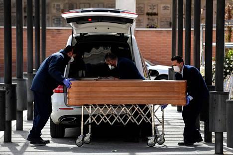 Hautausurakoitsijat vievät koronavirukseen menehtyneen vainajan arkkua krematorioon hengitysmaskit kasvoilla Madridissa maaliskuun 24. päivänä.