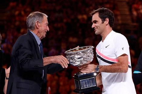 Ashley Cooper ojensi Australian avoimen tennisturnauksen voittopokaalin Roger Federerille vuonna 2018.
