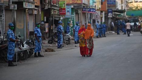 Musliminaiset kävelivät hengityssuojaimia käyttäneiden turvallisuusjoukkojen ohi Intian Ahmedabadissa sunnuntaina 12. huhtikuuta.