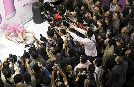 Messuvieraat ottivat kuvia mallista seksimessuilla Shanghaissa.
