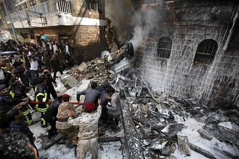 Armeijan henkilökunta ja palomiehet sammuttivat maahan syöksyneen hävittäjän aiheuttamaa tulipaloa Sanaassa tiistaina.