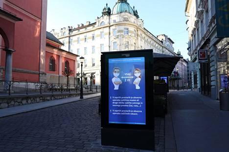 Ilmoitus Slovenian pääkaupungin Ljubljanan kadulla kehottaa pitämään etäisyyttä muihin.