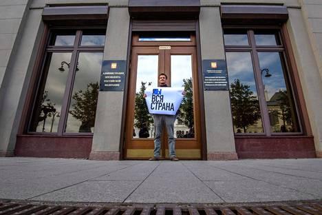 Mielenosoittaja kannatteli Pavel Ustinovia tukevaa kylttiä Venäjän presidentinhallinnon edessä maanantaina. Mielenosoittajat pitivät kylttiä yksi kerrallaan, sillä viranomaiset sallivat yhden ihmisen mielenosoitukset ilman lupaa.