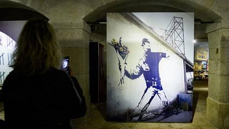 Valokuva vuonna 2005 seinään tehdystä Flower Thrower -graffitista oli esillä näyttelyssä Portossa maaliskuussa 2019.