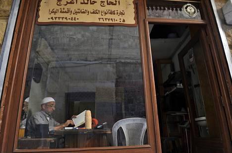 Syyrialainen mies luki Koraania taistelujen pauhatessa Aleppon kaupungissa torstaina.