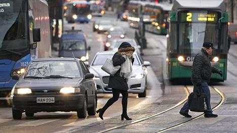 Jalankulkijoita suojatiellä ylittämässä ajorataa ja raitiotietä Helsingin Töölössä.