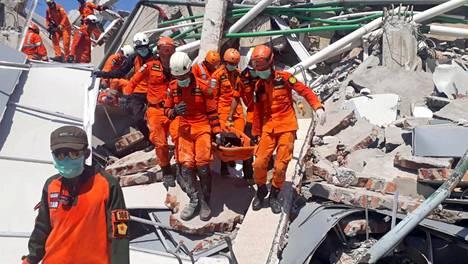 Pelastustyöntekijät kantoivat ruumista hotelli Roa Roan raunioista Palussa sunnuntaina.
