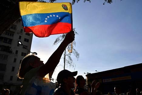 Tammikuussa virkaa tekeväksi Venezuelan presidentiksi julistautuneen Juan Guaidón kannattaja heilutti Venezuelan lippua pääkaupunki Caracasissa perjantaina.