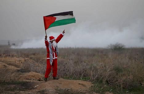 Joulupukiksi pukeutunut mielenosoittaja piteli Palestiinan lippua ja Israelin sotilaat levittivät kyynelkaasua tiistaina Gazan rajan tuntumassa mielenilmauksessa, jossa vastustettiin Yhdysvaltojen päätöstä tunnustaa Jerusalem Israelin pääkaupungiksi.