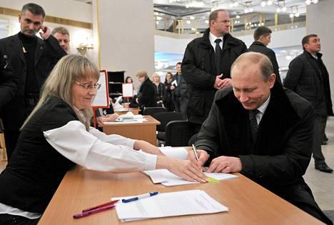 Pääministeri Vladimir Putin äänesti turvamiesten tiukassa vartioinnissa Moskovassa lauantaina.