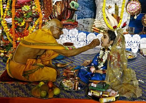 Hindupappi tarjoaa makeisia viisivuotiaalle tytölle, joka on puettu Kumariksi, neitsytjumalaksi. Rituaali kuuluu osana Kolkatan Durga Puja -festivaaliin, Bengalin hindujen suurinta juhlaa.