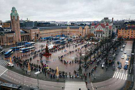Lukuisat ihmiset jonottivat aatonaattona Hurstinavun jouluruokakasseja Rautatientorilla.