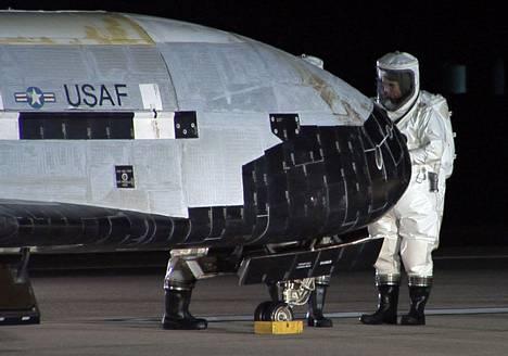Insinöörit suorittamassa toimenpiteitä X-37B-sukkulalle laskeutumisen jälkeen joulukuussa 2010. Sukkula laskeutui Vandenbergin lentotukikohtaan Kaliforniassa vietettyään 224 päivää maata kiertävällä radalla.