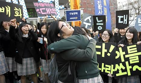 Lukiotytöt kannustavat loppukokeeseen menevää ystäväänsä koepaikan edustalla Soulissa.