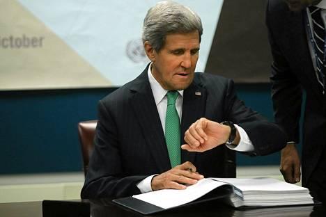 Yhdysvaltain ulkoministeri John Kerry tarkisti ajan kellostaan ennen kuin hän allekirjoitti asekauppaa rajoittavan sopimuksen New Yorkissa keskiviikkona.