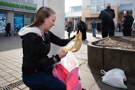 Opiskelija Laura Linnola tutustui ruokakassinsa sisältöön ostoskeskuksen aukiolla.