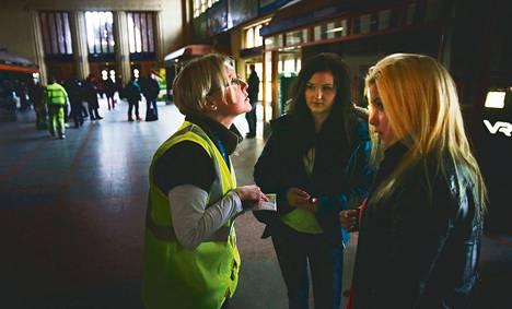 Minka Holmström (oik.) ja Meeri Virtaanvuori saivat tiedon junan <br />lähtöajasta VR:n työntekijältä Helsingin päärautatieasemalla.