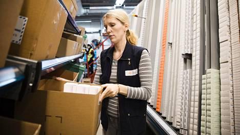 Ene Madisson lataa lääkkeitä A-frame-keräysautomaattiin. Automaatti osaa sylkeä apteekin tilaamat lääkkeet keskellä kulkevalle hihnalle sekunnin murto-osan tarkkuudella niin, että ne saapuvat hihnan päässä olevalle keräyslaatikolle yhtenä kasana.