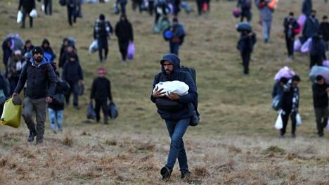 Lipan leirin asukkaat kävelivät kohti läheistä metsää leirin palon jälkeen joulukuun lopussa.