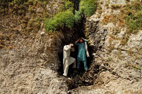 Miehet yrittivät viilentäytyä pienen vuoripuron alla Pakistanin Torkhamissa.