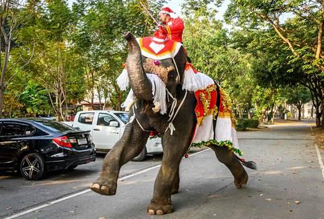 Jouluisesti koristeltu elefantti matkalla jakamaan joululahjoja koululaisille Thaimaan Ayutthayassa aatonaattona maanantaina.