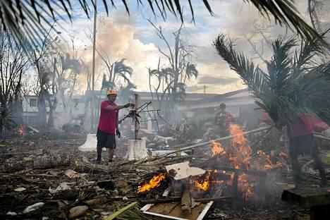 Punaisen ristin vapaaehtoiset työntekijät polttivat romahtaneiden talojen jäänteitä Taclobanissa 20. marraskuuta.