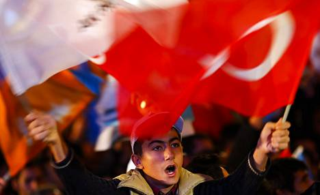 Nuorukainen juhli vaalivoittoa islamilaisen AK-puolueen päämajan edustalla sunnuntaina Ankarassa.