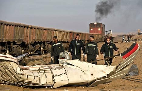 Pelastustyöntekijät tutkivat maanantaina onnettomuuspaikkaa, jossa juna törmäsi hääseurueeseen Kairon eteläpuolella.