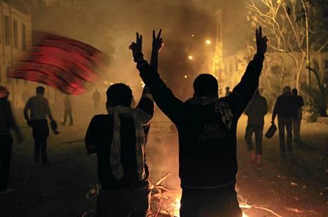 Mielenosoittajat näyttivät voitonmerkkiä sisäministeriön rakennuksen edustalla Kairossa myöhään torstai-iltana.