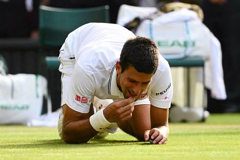 Novak Djokovic juhli voittoaan syömällä Wimbledonin areenan nurmea.